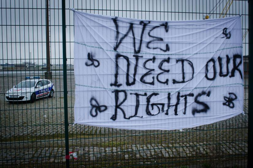 "A sheet on a fence with the words ""We need our rights"" written on it. Behind the fence a police car"